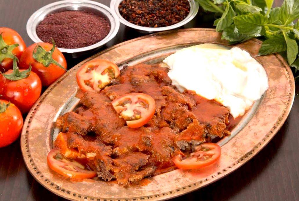 İskender Kebab, servit pe platou de arama, cu bucati de carne in sos de rosii, impreuna cu iaurt, si langa doua boluri de condimente, la restaurant Divan