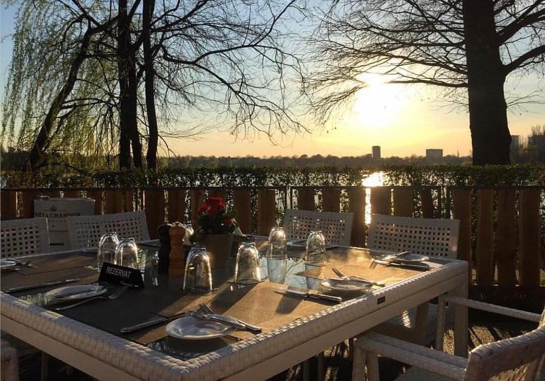 masa alba cu farfurii si pahare, iar in fundal copaci si lacul herastrau, fotografiata la apus, la restaurant La Brasserie Bistr&Lounge, unul din restaurante franțuzești din București