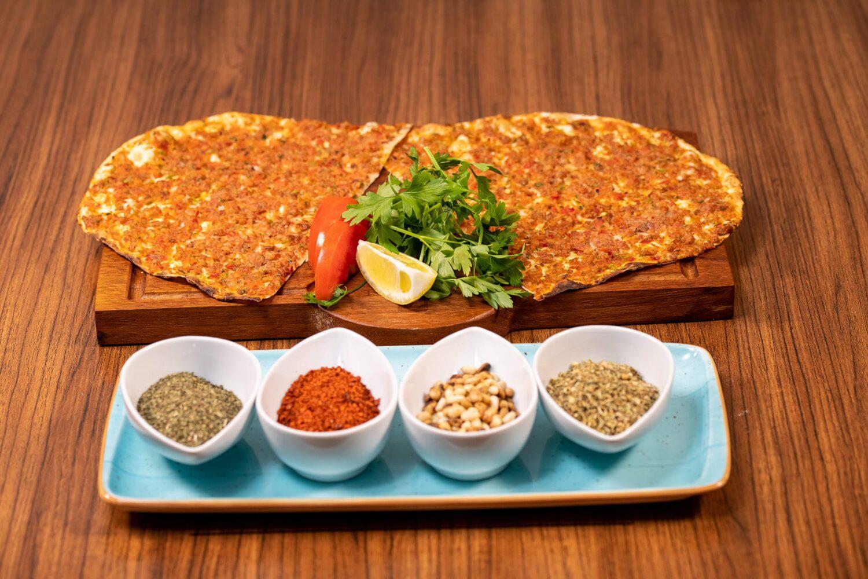 lachmacun servit pe un tocator de lemn, alaturi de 4 boluri cu diverse sosuri, la Turquoise Restaurant