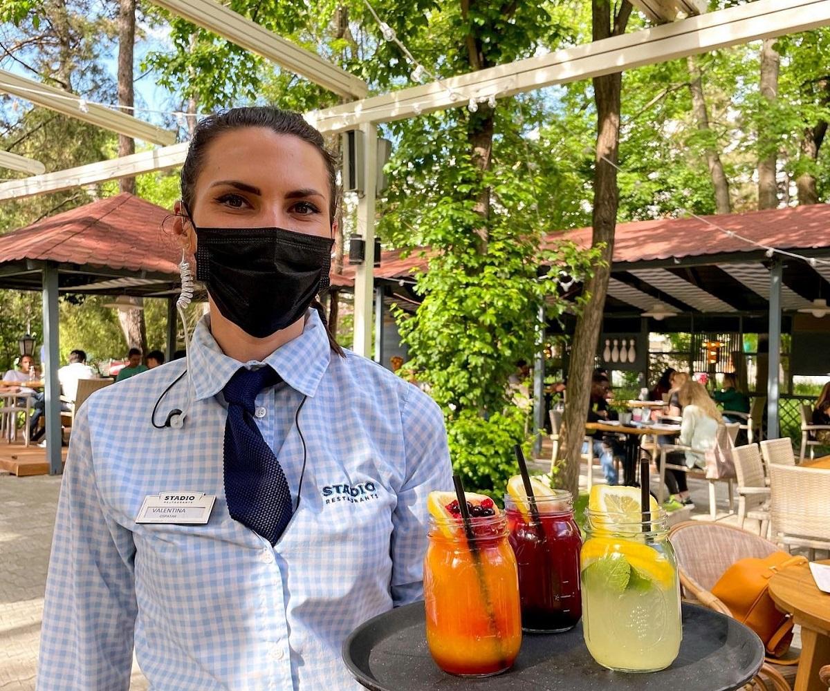 Femeie ospătar in uniforma, cu masa, care tine in mana o tava cu trei limonade pe terasa restaurantului Stadio Park