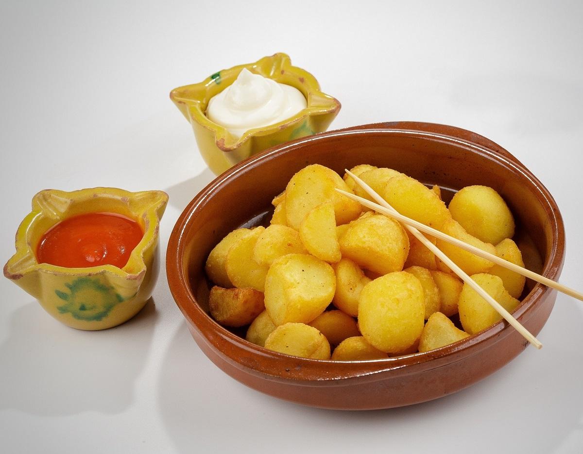 Bol maro in care sunt asezati Patatas Bravas, cartofi aurii, crocanti, iar langa un bol mai mic cu sos rosu iute