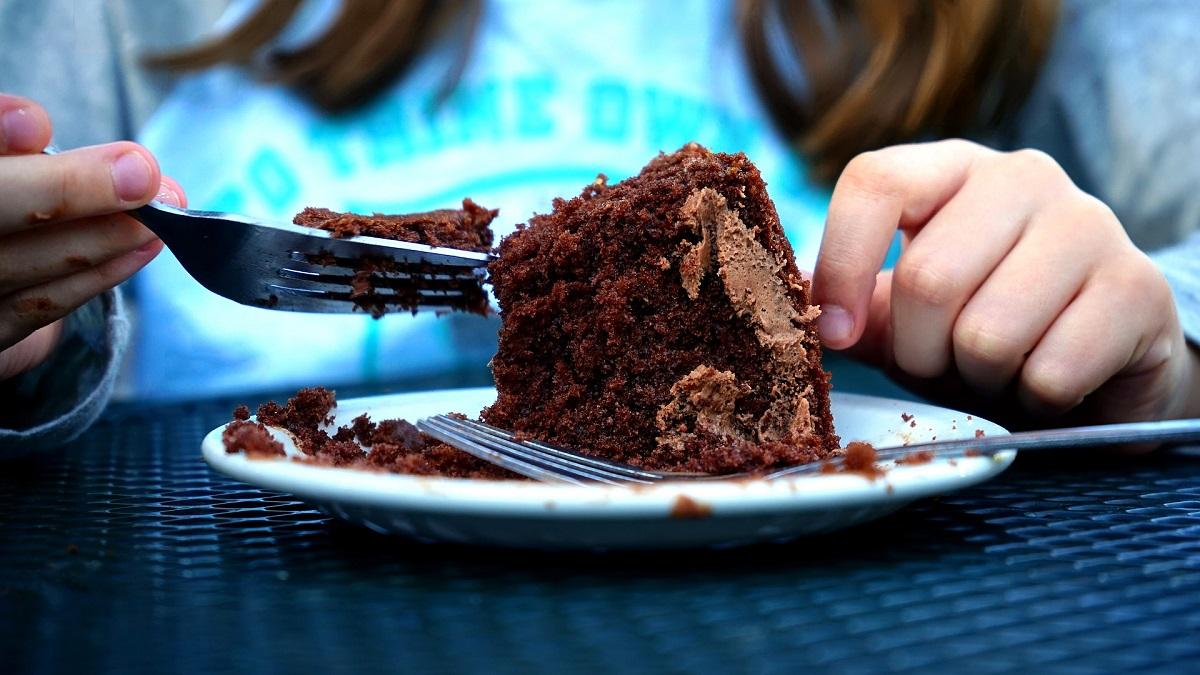 closeup cu o felie de prăjitură de ciocolată într-o farfurie din care mănâncă o femeie imbracata in albastru