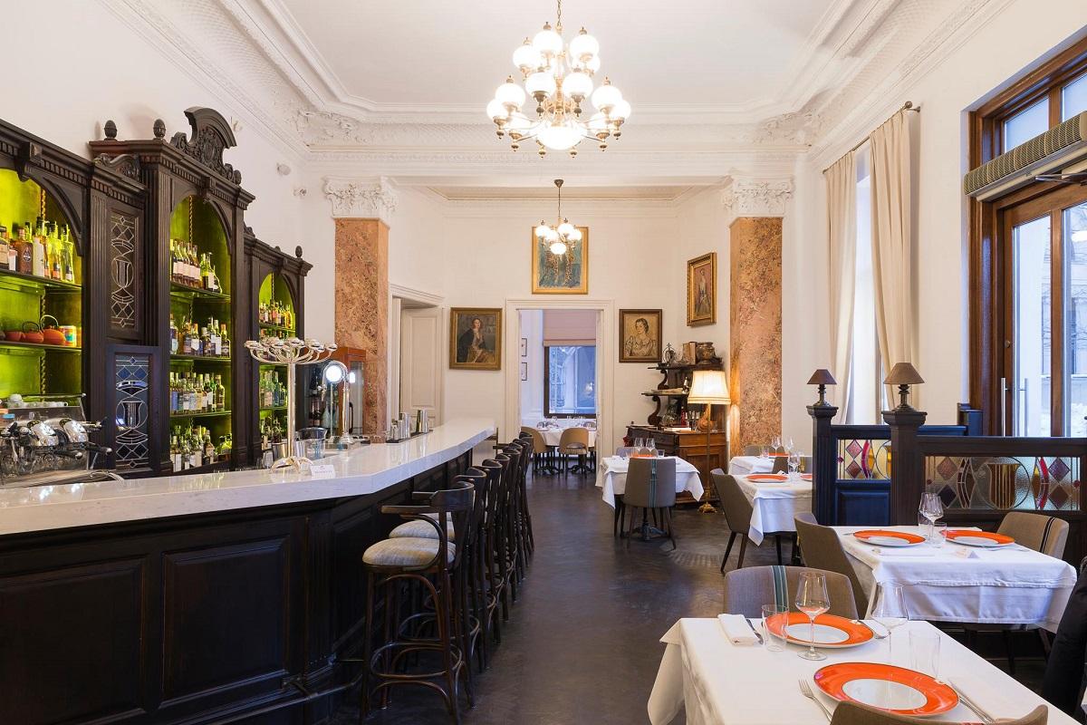 sala de mese de la Relais & Châteaux Le Bistrot Français, cu barul in stanga si mese pe partea dreapta, in partea geamurilor, unul din restaurante franțuzesști din București, decorat in stil clasic