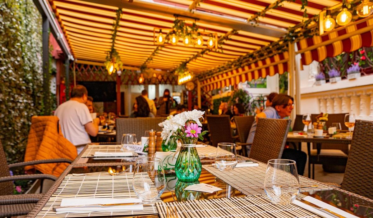 Terasa cu copertina, o masa in plin plan de la restaurant Mon Paris, cu stergare si pahare pe masa si o vaza cu flori, iar in fundal oameni asezati la alte mese.