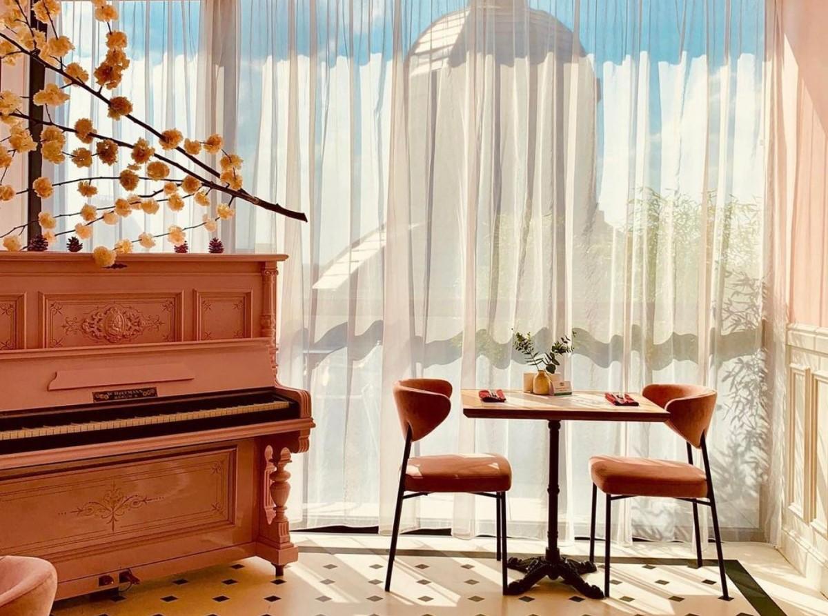 o masa cu doua scaune asezata in fata unui perete din geam, prin care se vede cupola unei cladiri, iar langa masa se afla un pian, la Cișmigiu Bistri București, restaurant franțuzesc din București