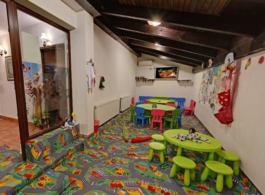 camera amenajata ca loc de joaca la restaurantul TAverna Sarbului din București, cu msaute verzi de plastic si scaunele, covor colorat si televizor pe perete