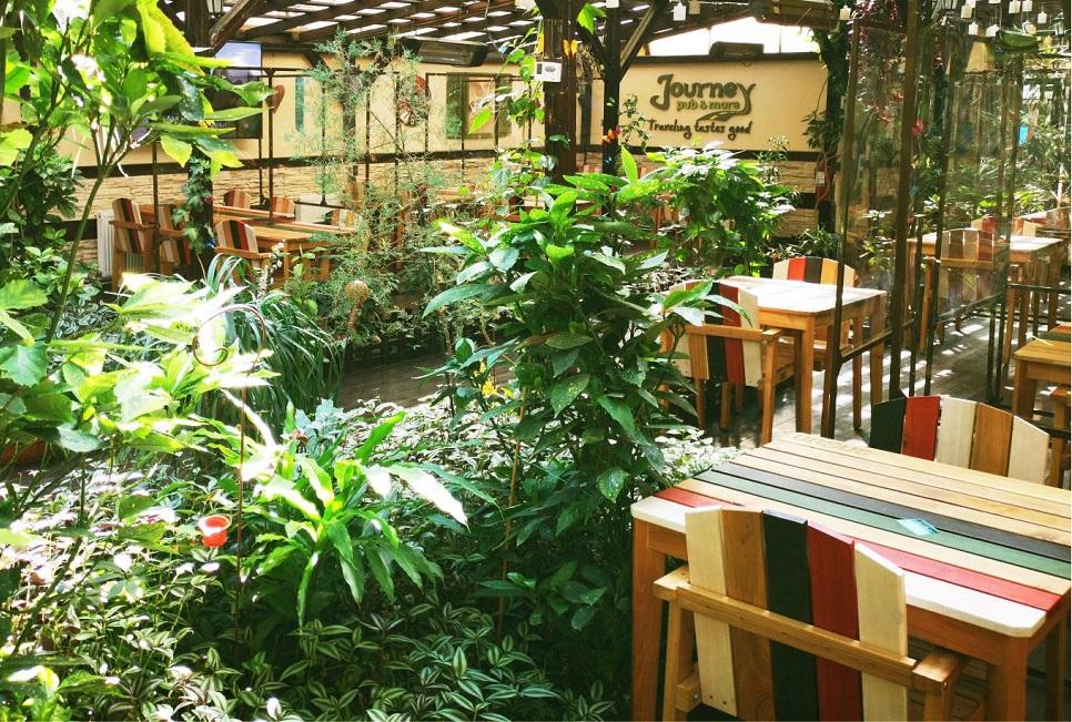 terasa de la Journey Pub din București, plină cu flori, cu mese si scaune din lemn, cu stinghii colorate diferit, una din restaurante și terase child friendly din București