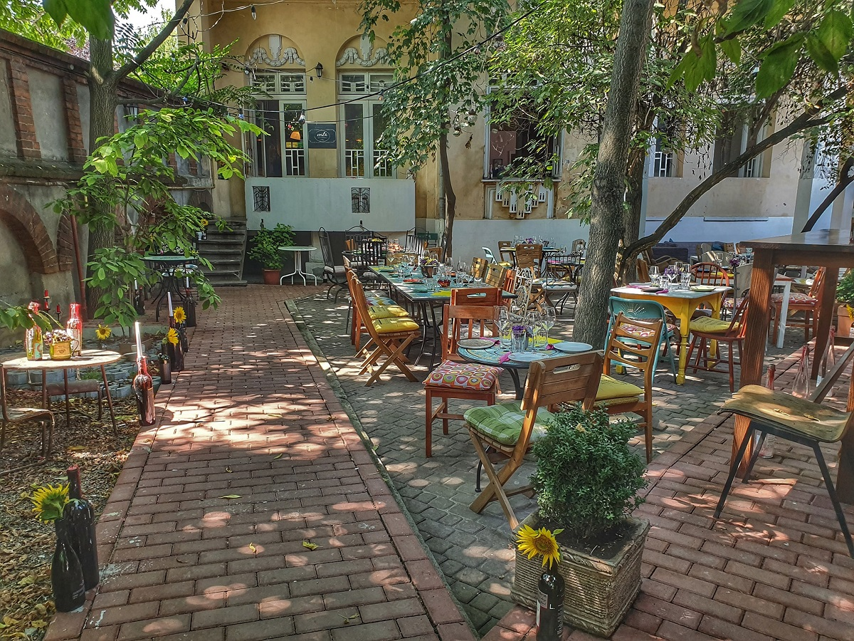 Curtea restaurantului frantuzesc Voila Le Bistrot, cu mese si scaune colorate si copaci in curte, iar in fundal o casa cu tencuiala galbena
