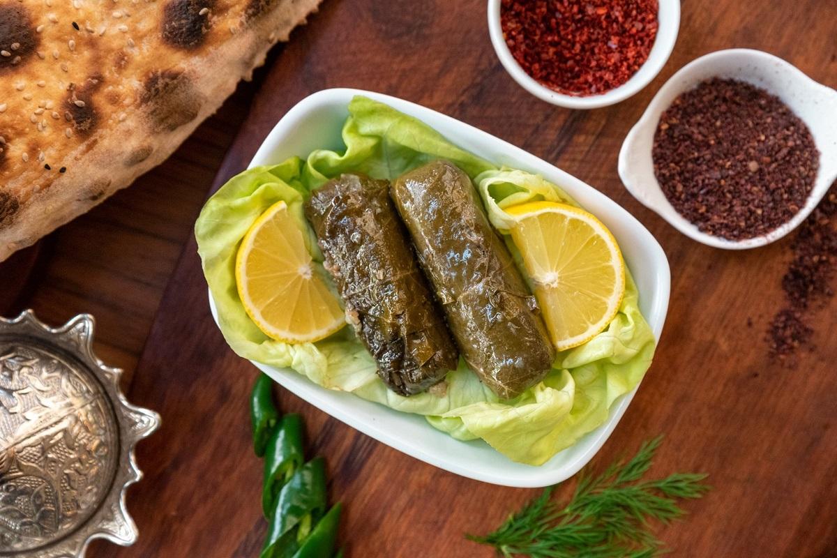 Yaprak Sarmasi, sarmale in foi de vita, servite pe o farfurie alba alturi de foi de salata si felii de lamaie, asezate pe un fundal din lemn, la Turquoise Restaurant