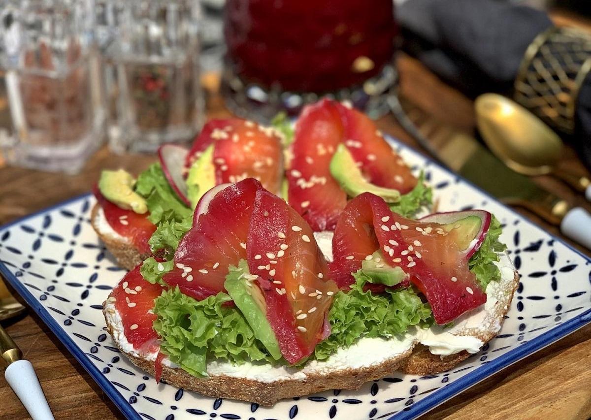 Nordic Open Sandwich  de la Il Locale, cu somon Gavrilax făcut în casă, cremă de brâznă și avocado, servit pe o farfurie alb cu albastru