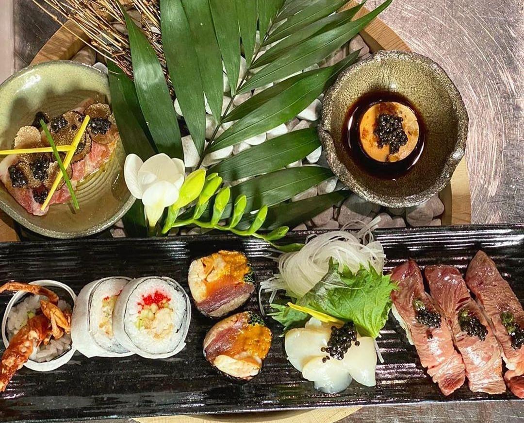 Platou cu sushi de diverse forme si in diverse combinatii, cu sosuri si decorat cu o frunza de palmier, la Argentine Steak & Sushi Bucuresti