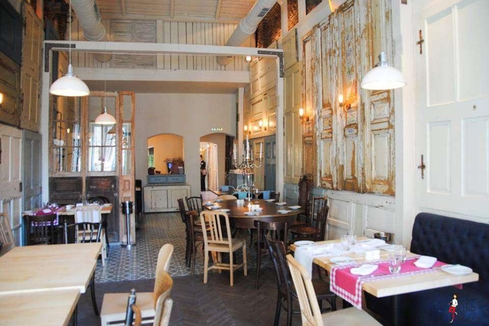interiorul restaurantului Aubergine, unul din retsaurante vegetariene București, cu pereti decorati cu obloane albe patinare, mese cu scuane retro