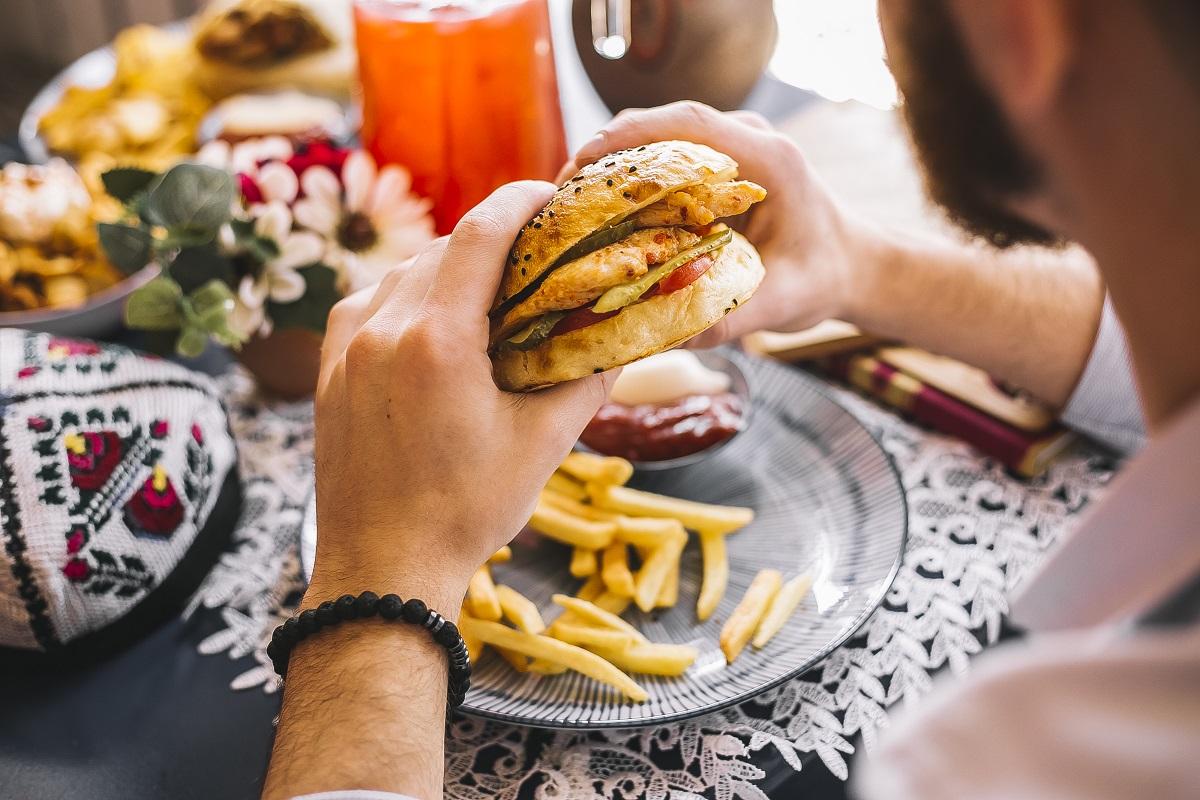 Barbat care tine in mana un burger de pui servit cu cartofi si sos, imagine reprezentativa pe locuri din București cu sandviș bun