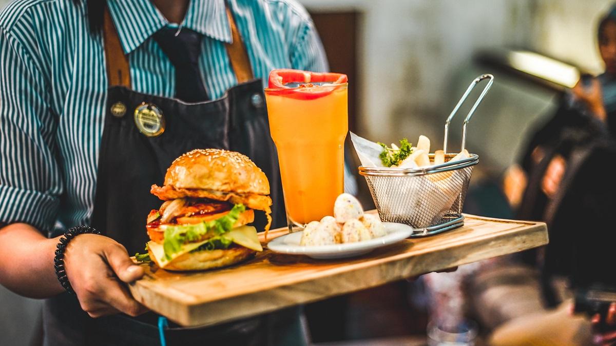 ospatar care serveste un burger, impreuna cu un pahar de cocktail portocaliu si cartofi pe un tocator de lemn, ca idee pentru când e ok să refuzi mâncarea la restaurant