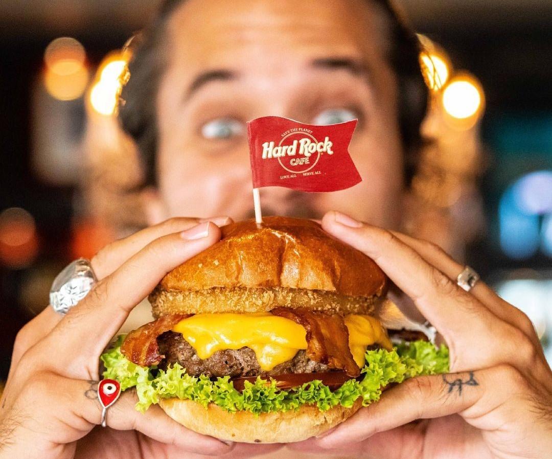 Close-up cu un barbat care tine in maini un burger de la hard rock cafe si se pregateste sa muste din el, unul din preparate emlematice de la acest local.