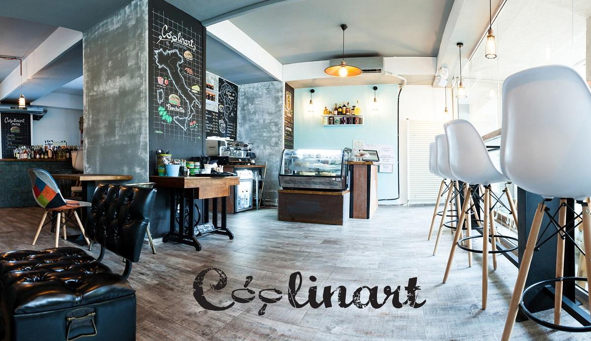 interiorul de la Coolinart, unul din restaurante vegetariene București, cu pereti negri desenati cu creta, mese din lemn si scaune negre