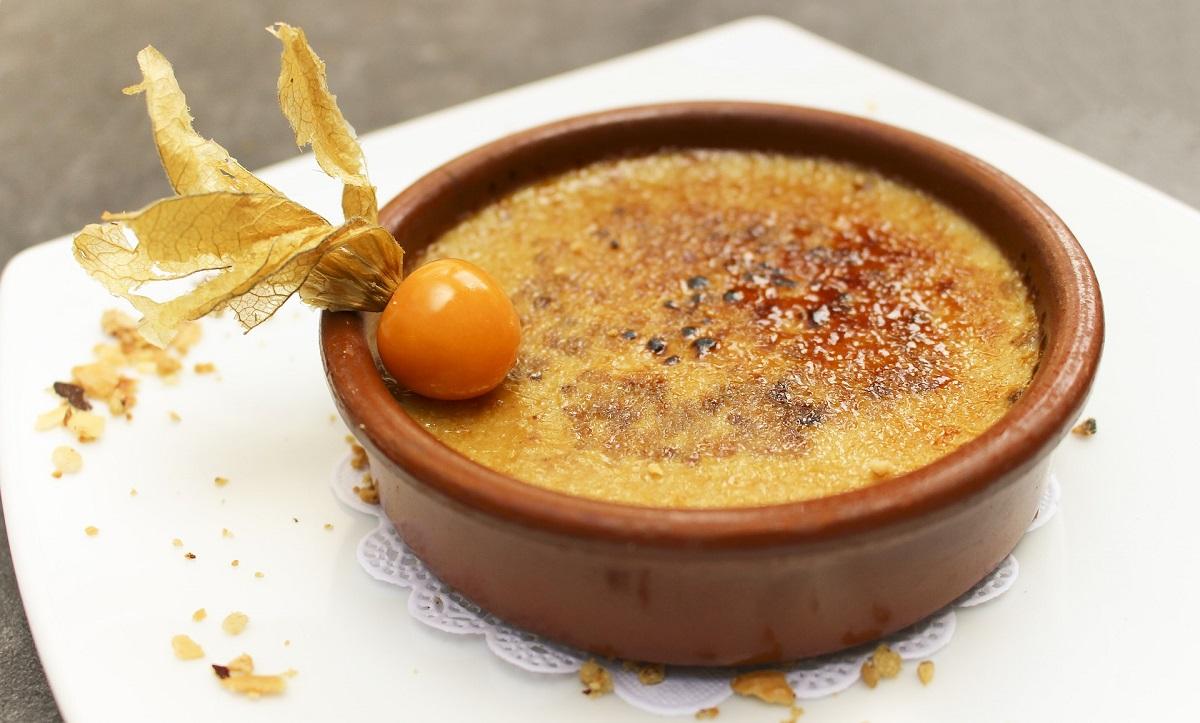 creme brulee in vas de teracota deocrat cu fructul pasiunii, in care se vede diferența între Crème brûlée și crema de zahăr ars datorită aspectului cu crustă de zahăr