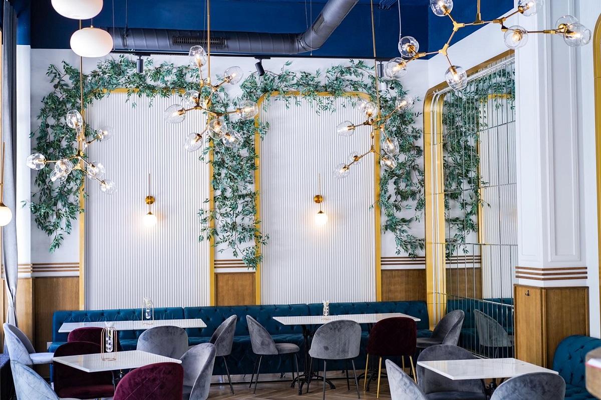 Restaurantul Ergo din București, cu pereti albi in stil clasic, pe care sunt arcade din plante si lampi ambientale, cu mese albe, scaune si canapele