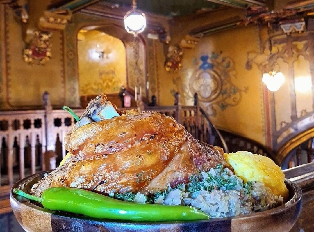 Prim plan cu farfurie cu ciolan de porc crocant, varza calita si ardei iute, iar in fundal decorul din restaurant