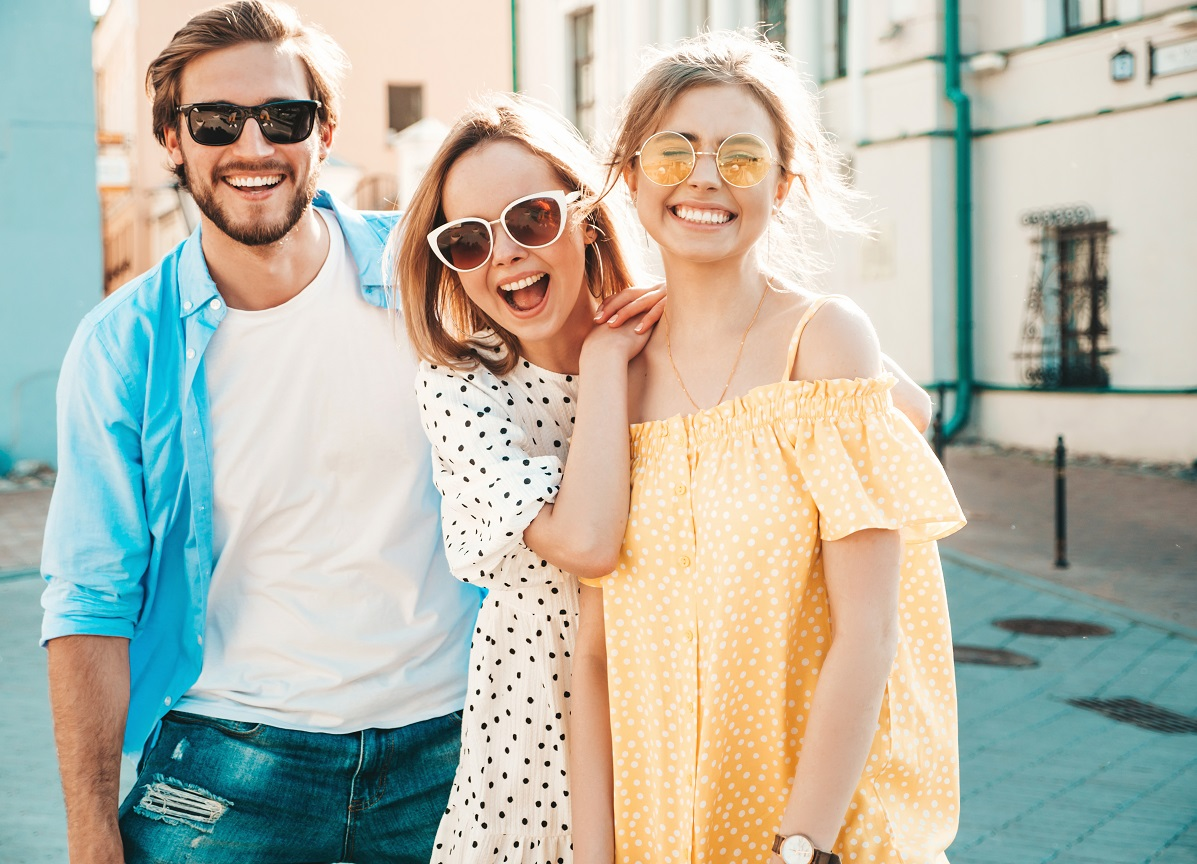 Grup de prieteni, un baiat si doua fete, imbracati in haine de vara, cu ochelari de soare, care sugereaza o iesire in oras in weekend