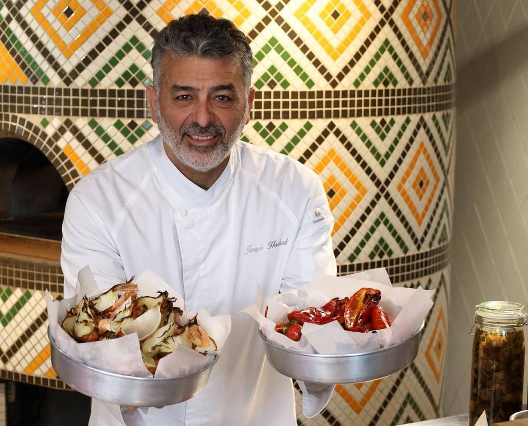 Chef Joseph Hadad imbracat in uniforma de bucatar, tine in mana doua platouri metalice cu mancare orientala, in restaurantul Mace