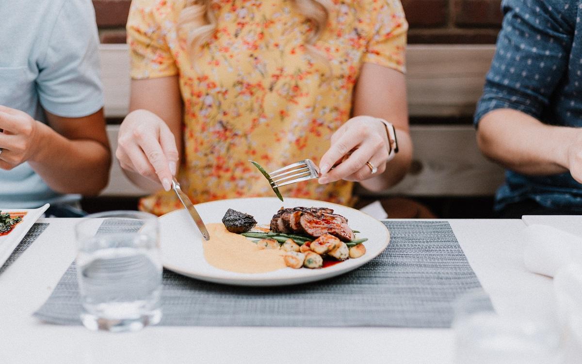 femeie careia nu i se vede capul, care manaca dintr-o farfurie asezata pe o masa gri, asezata intre doi barbati, la restaurant