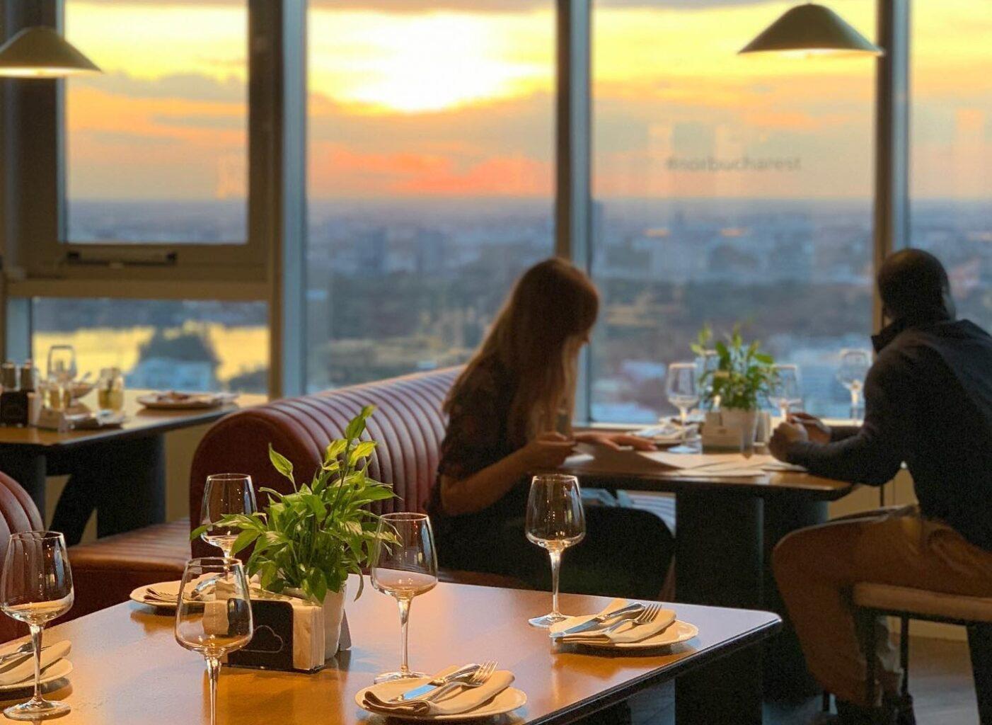 Prim plan cu o masa goala de restaurant, cu pahare asezate pe masa si servetele, iar in fundal o masa la care ia cina un cuplu, in fata unor ferestre mari prin care se vede apusul si panorama asupra orasului, la NOR Sku Casual Restaurant din București
