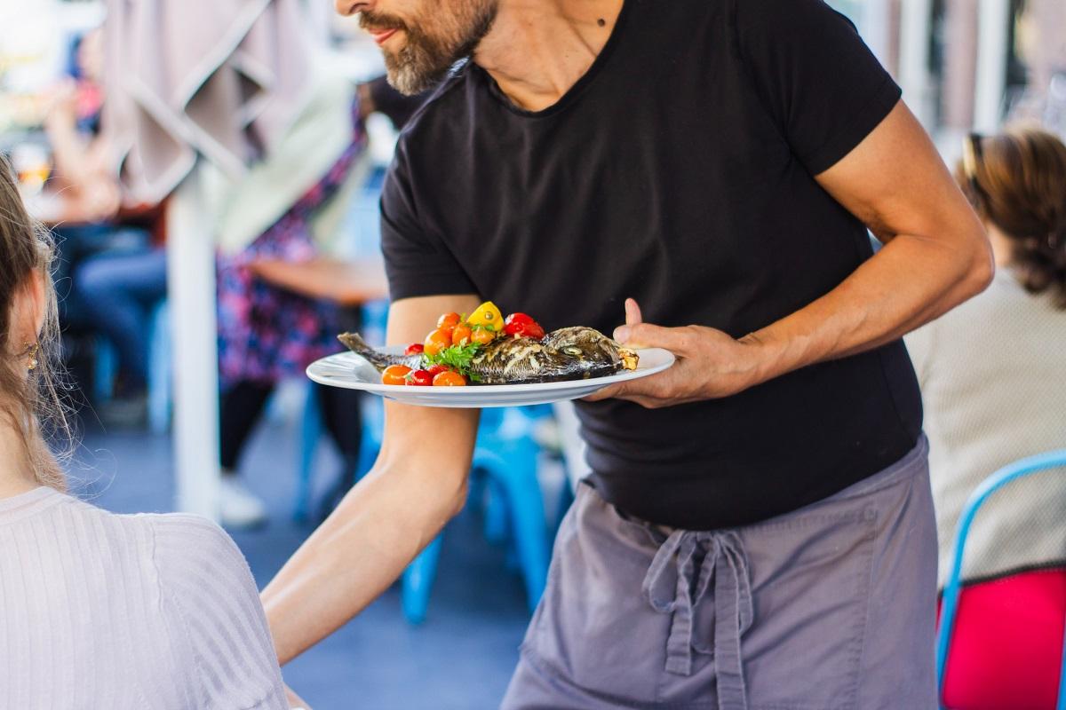 Ospatar cu tricou negru si pantaloni gri, care serveste la masa o farfurie cu peste si legume, la terasa, imagine reprezentativă pentru când să refuzi mâncarea la restaurant