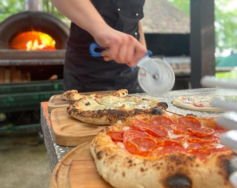 Imagine din pizzeria Pizza Mania, cu doua pizza asezate pe tocatoare de lemn si un pizzar care taie felii cu cutitul de pizza, iar in fundal un cuptor pe lemne aprins