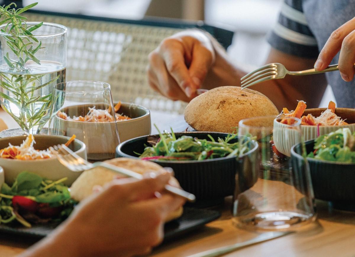 close up cu o masa pe care sunt asezate boluri cu salata si doua farfurii din care mananca doi oameni, cu burger, la Samsara unul din restaurante vegateriene București