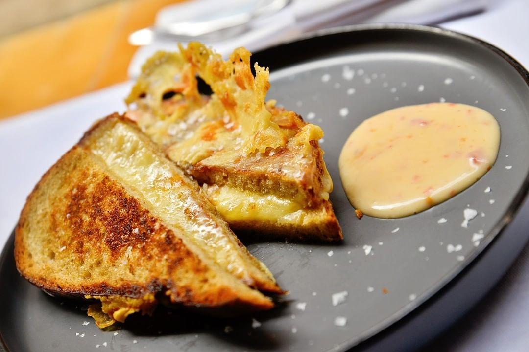 Toast din Felii de pâine cu maia, bine unse cu unt și asortate cu brânză caldă de Comté și Cheddar