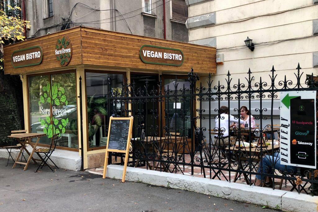 sara green victoriei, unul din restaurante vegetariene București, cu intrarea in terasa, imprejmuita cu gard din fier forjat si localul cu ferestre mari si stalpi de lemn pe care este trecuta firma