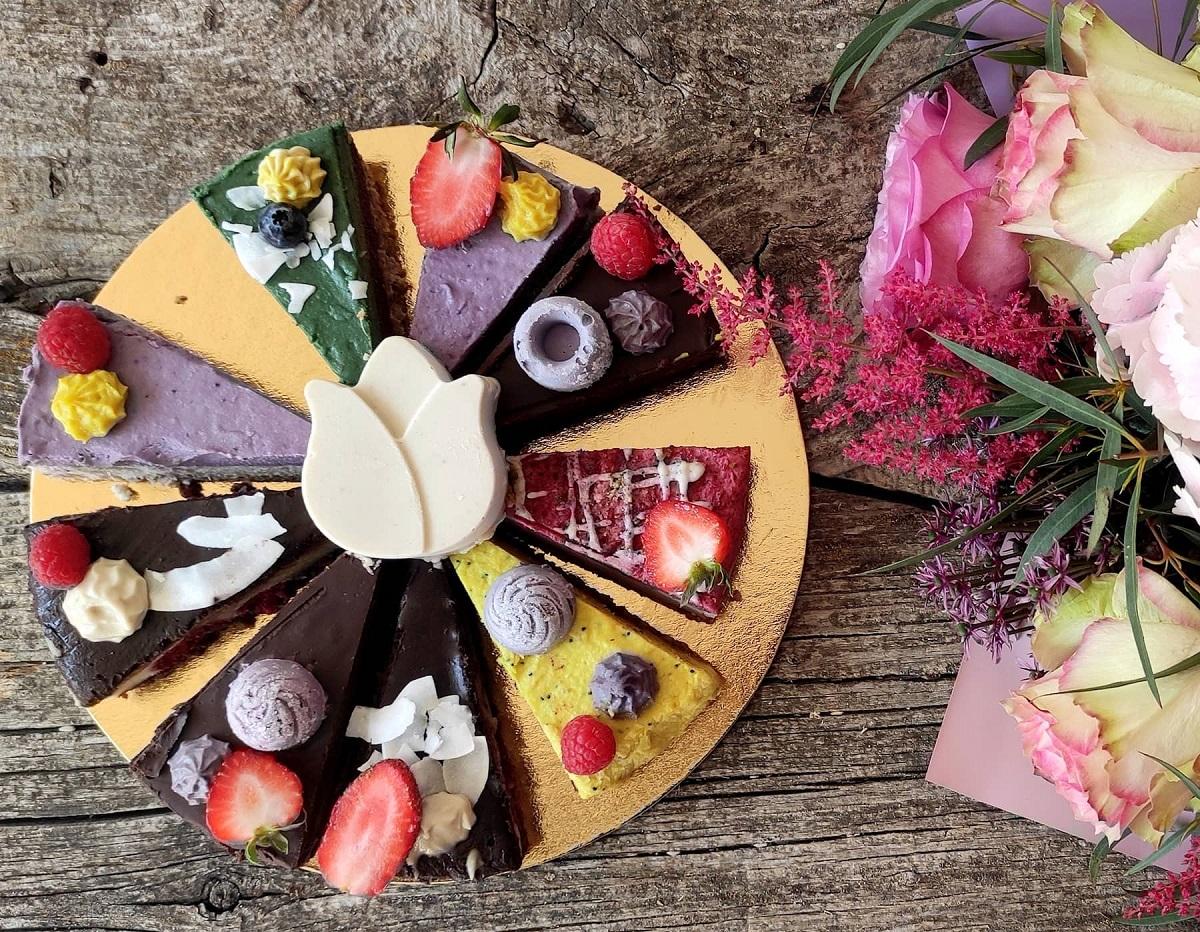 platou cu felii de tort vegan si vegetarian, de difertite sortimente si culoti, ornate cu fructe, fotografiate de sus, langa un buchet cu flori in nuante mov