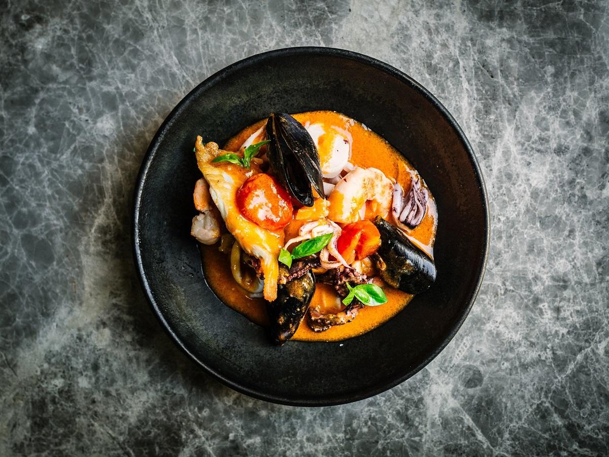 Farfurie neagra pe fundal gri, fotografiata de sus, cu tocana din sos de rosii, dorada, creveti, calamari, scoici, unul din preparate emblematice la Raionul Floreasca din București.