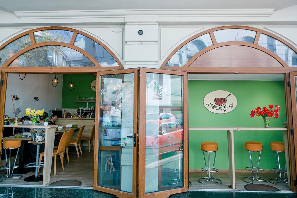 Vyro Raw Vegan fotografiat de afara, cu doua ferestre mari gen arcada, deschise larg, prin are se vede interiorul restaurantului, cu scaune inalte si pereti verzi