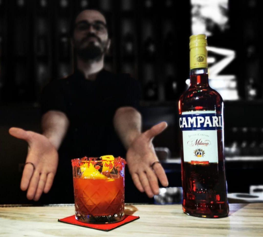 Adrian Bologa in fundal intunecat, care arata cu mainile catre un apahar de cocktail Negroni, langa o sticla de Campari, în cadrul Negroni Week