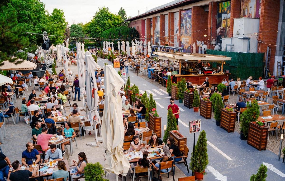 Imagine de ansamblu de pe terasa de la Berăria H, cu oameni care stau la mese cu umbrele stranse