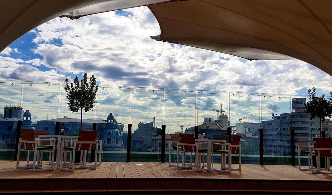 terasa de la aria tnb, cu mese asezate pe podea inaltata din lemn, umbrele mari si priveliste catre Centrul Bucureștiului