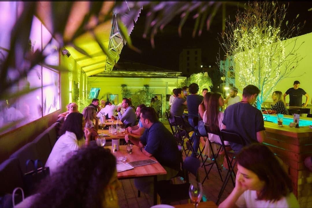 Oameni asezati la mese si la bar la Balkon Resto Garden, cluminata in verde, unul din restaurante la înălțime din București