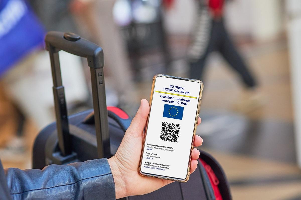 certificat verde digital covid afisat pe ecranul unui telefon mobil tinut in mana de cineva