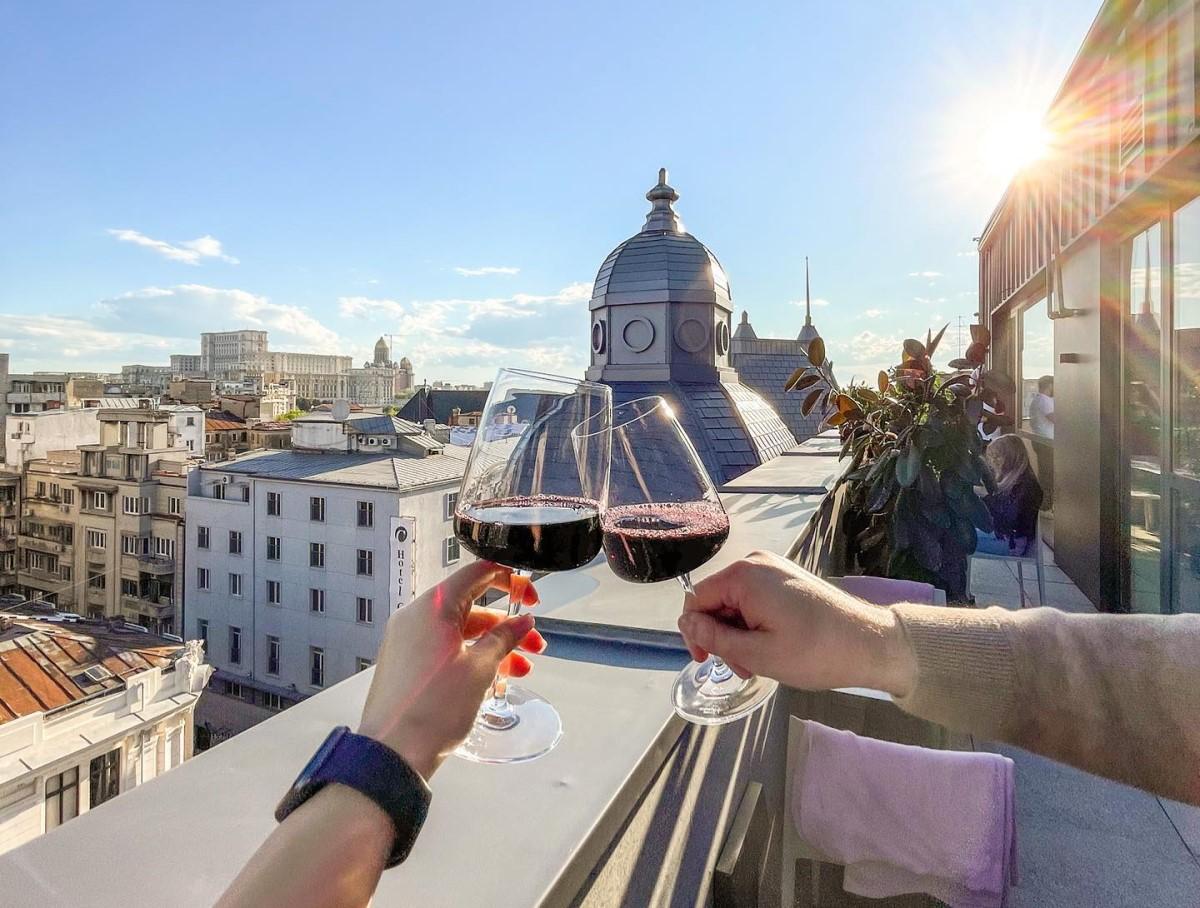 close up cu doua pahare ciocnite de un cuplu căruia i se vad doar mainile, iar pe fundal terasa Cismigiu Bistro de tip rooftop