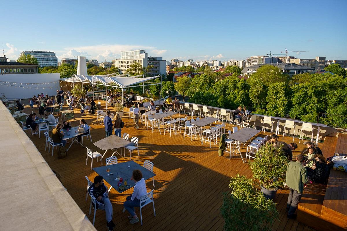 terasa Deschis Gastrobar fotografiata ziua, de tip rooftop, cu podea din lemn si multe mese, iar in fundal se vad multi copaci si blocuri in departare, unul din restaurante la înălțime din București