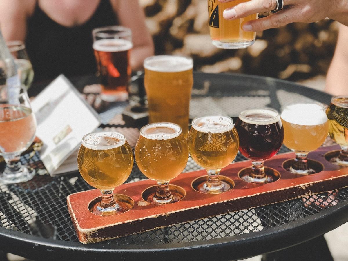 pahare de bere in diverse culori, asezate pe o tava portocalie, la festival de bere, recomandări de weekend București 11-12 septembrie