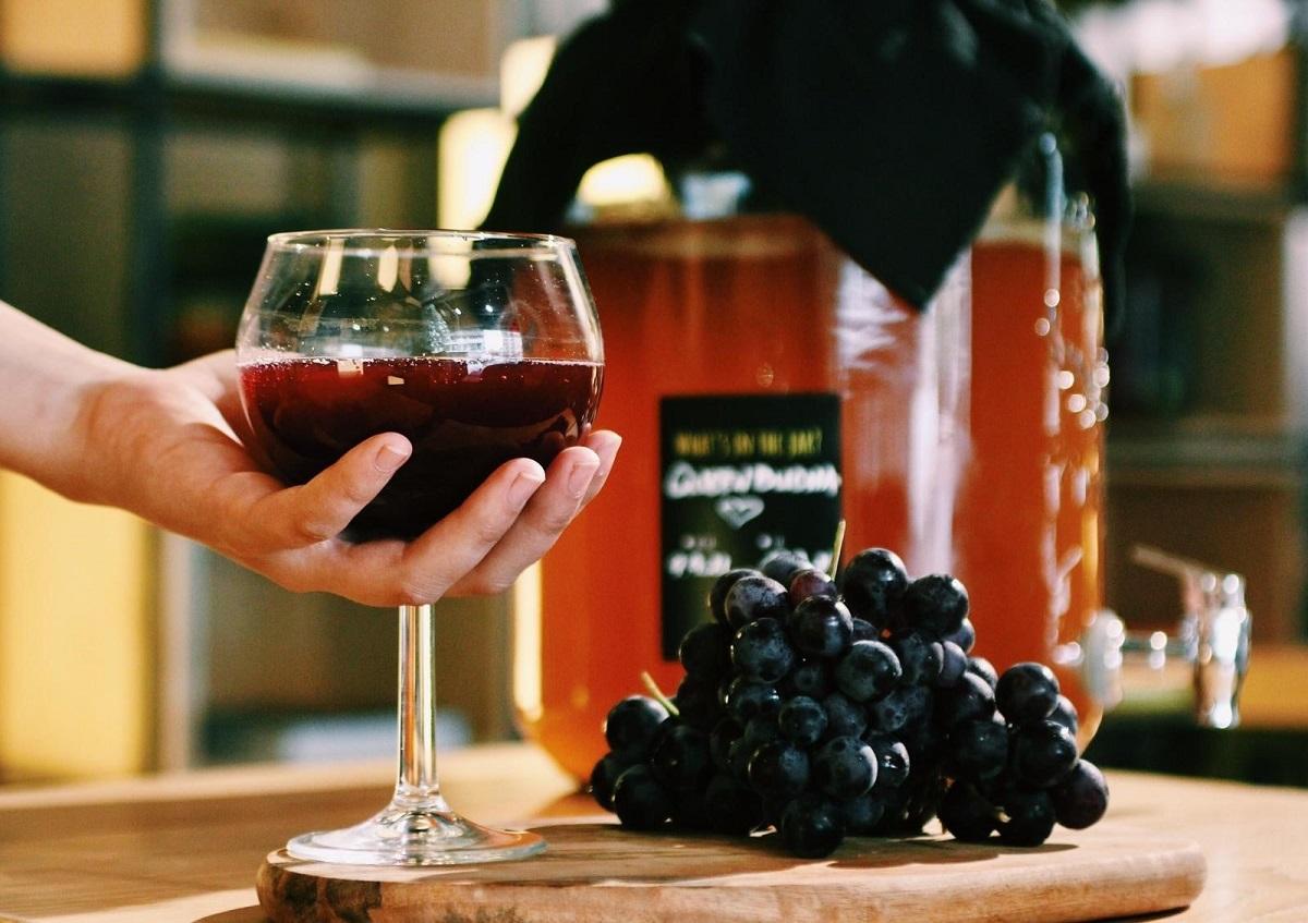 pahar de vin langa un platou cu struguri