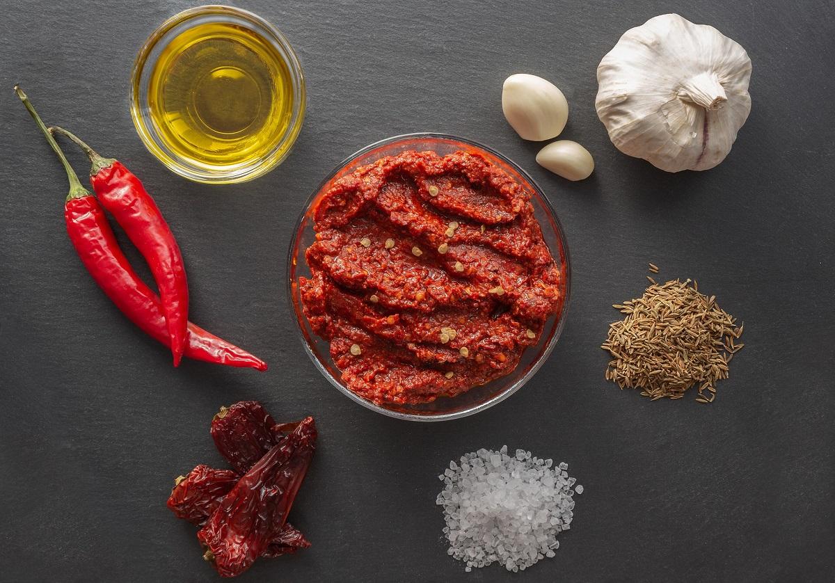 pasta harissa fotografiata de sus, intr-un bol pe fundal negru, alaturi de ardei iuti, ulei, usturoi, sare, condimente, unul din sosuri iuți