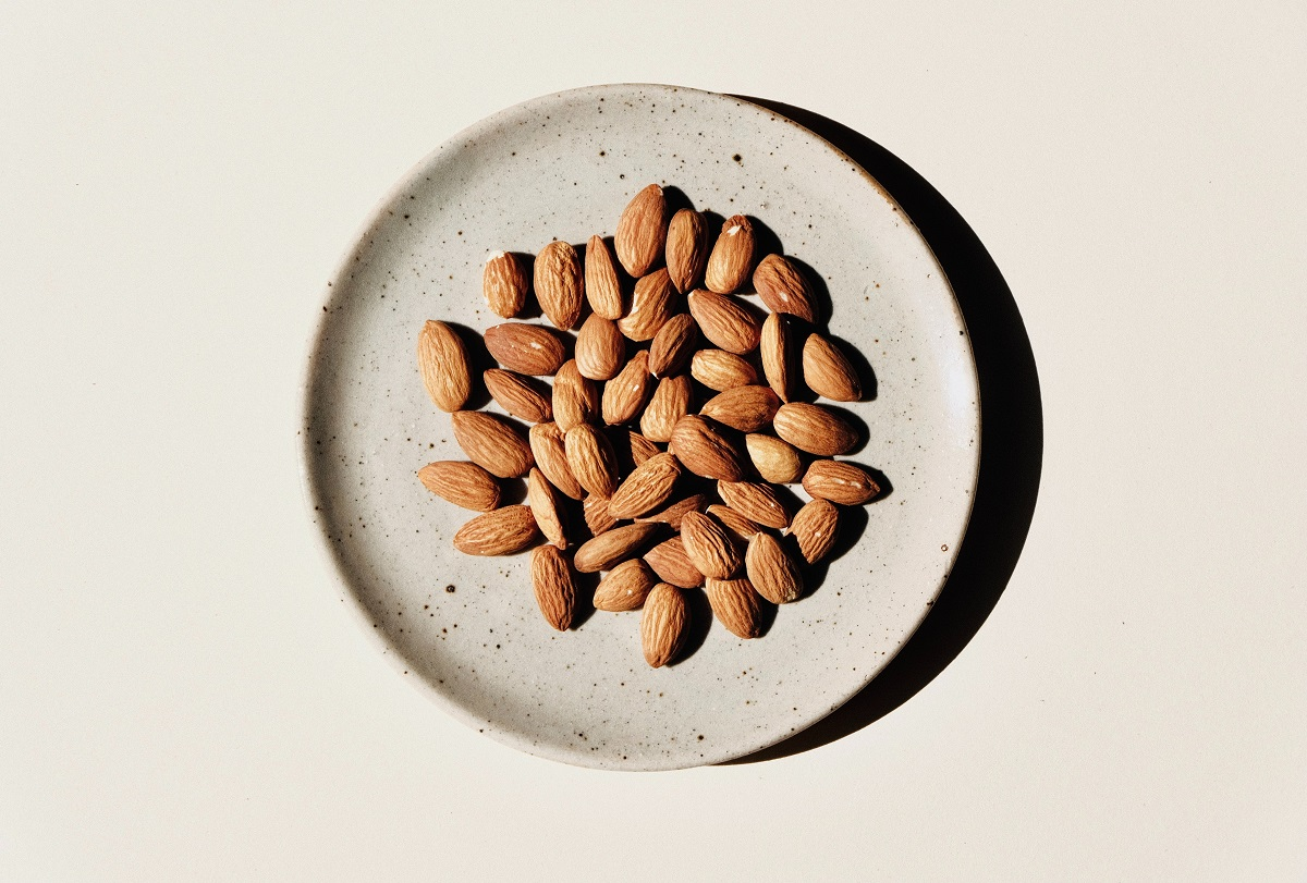 migdale in farfurie alba fotografiata de sus, unul din alimentele de toamnă care te ajută să dormi mai bine