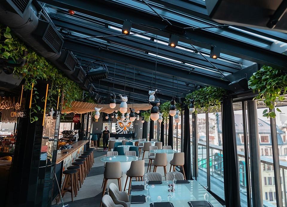 restaurantul Naive, cu barul in stanga si mese asezate de-a lungul peretelui din geamuri mari pe dreapta, cu acoperis tio rooftop, din geamuri