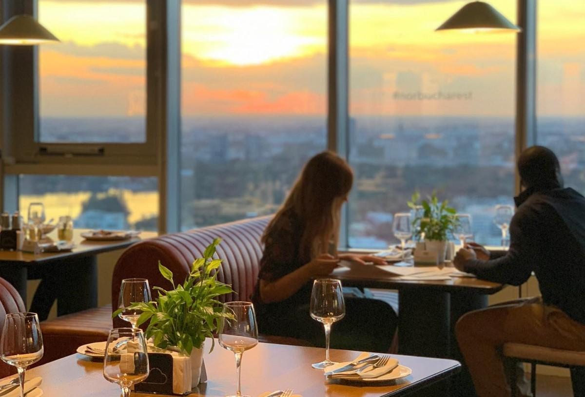 Cuplu care ia masa la restaurant in fata unor geamuri mari, la apus, cu vedere panoramica asupra orasuljui