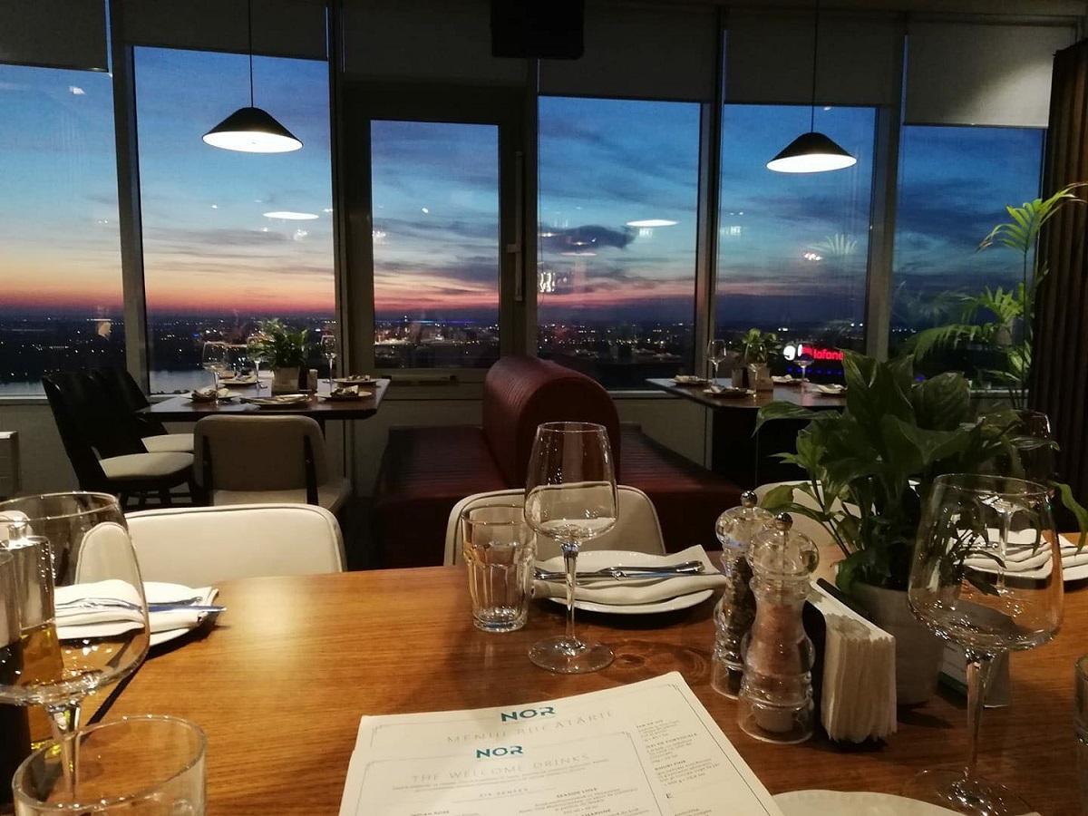 imagin din restaurantul la înălțime NOR din București, fotografiat la apus, cu mese si canapele si geamuri mari prin care se vedere orasul la venirea serii