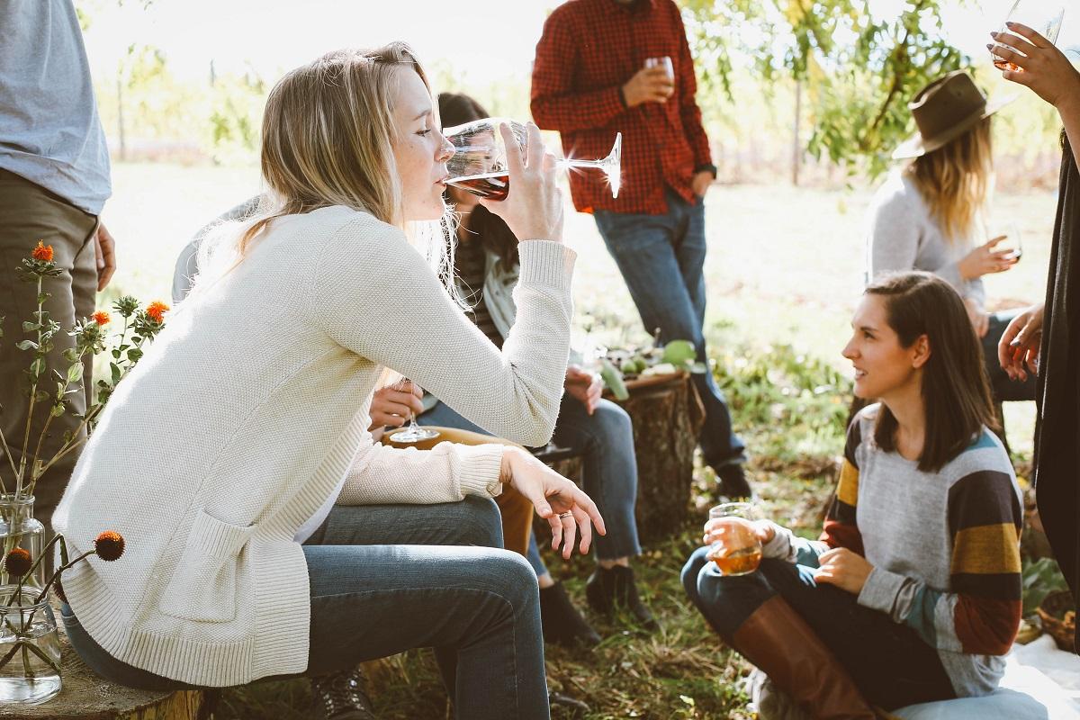 grup de tineri in natura, cu o femeie in prim plan, care bea dintr-un pahar de vin - recomandări de weekend